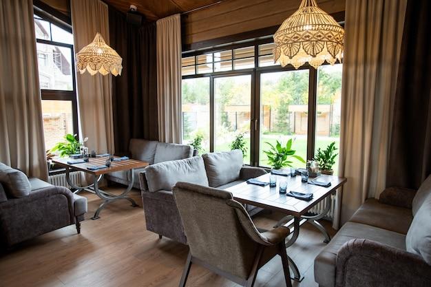 Dekoracyjne żyrandole zawieszone na suficie nad serwowanymi stołami oraz wygodne kanapy w przytulnej restauracji