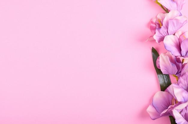 Dekoracyjni kwiaty na różowym tło składzie.
