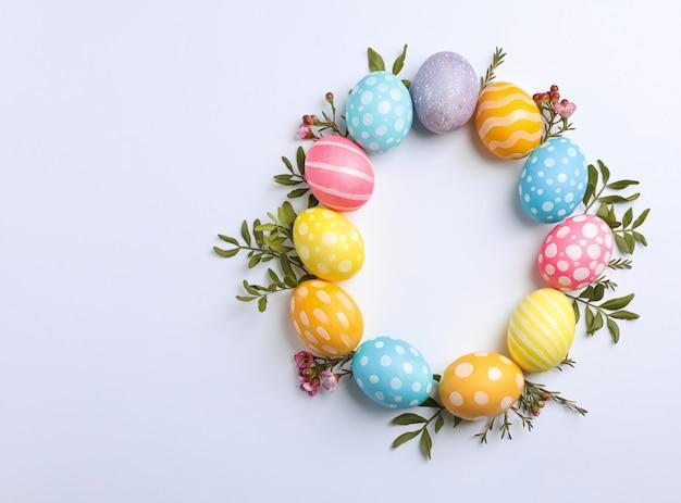 Dekoracyjni wielkanocni jajka i kwiaty na białym tle