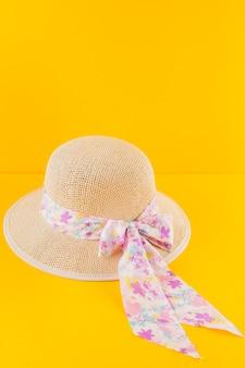 Dekoracyjny kapelusz na żółtym tle