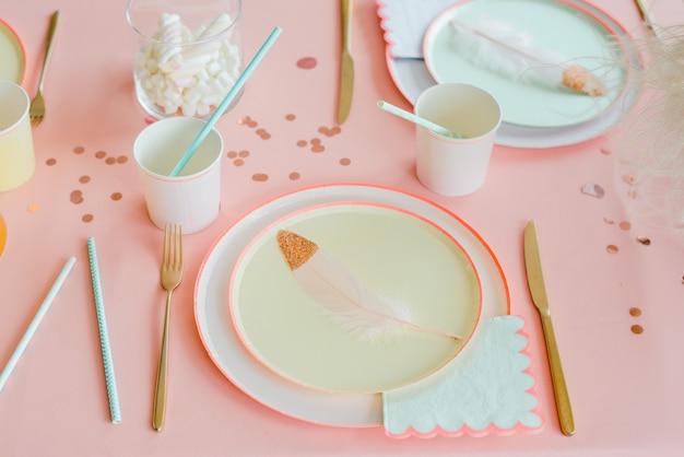 Dekoracyjny stół w pastelowych kolorach z różowym obrusem, papierowymi kolorowymi naczyniami, filiżankami, złotymi sztućcami. urodziny dla dziewczynki, chrzciny lub dekoracje na przyjęcie panieńskie.