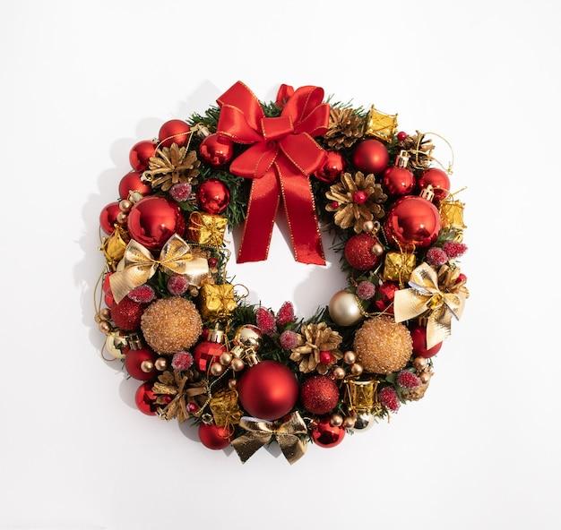 Dekoracyjny świąteczny wieniec z czerwonymi i złotymi zabawkami świątecznymi na białym tle