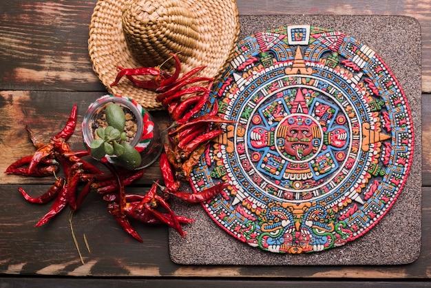 Dekoracyjny symbol meksykański na pokładzie w pobliżu suszonego chili i sombrero