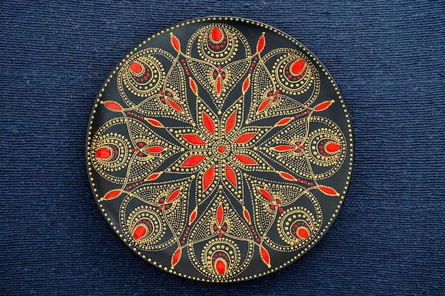 Dekoracyjny talerz ceramiczny w kolorach czarnym, czerwonym i złotym