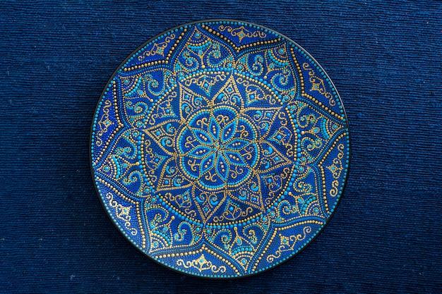 Dekoracyjny talerz ceramiczny w kolorach niebieskim i złotym, malowany talerz na tle niebieskiej tkaniny, zbliżenie. dekoracyjny talerz porcelanowy malowany farbami akrylowymi, rękodzieło