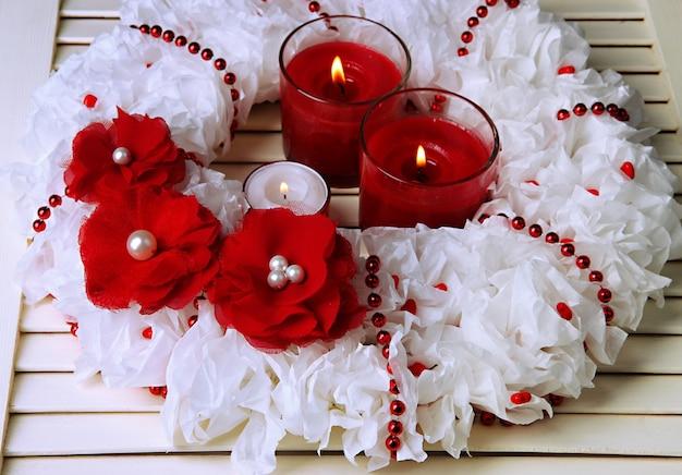 Dekoracyjny wieniec ze świecami na drewnianym tle