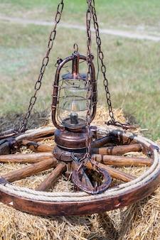Dekoracyjny żyrandol z koła wózka z łańcuchami i ukrytym okablowaniem na wiejskim dziedzińcu w letni dzień, zbliżenie, ukraina