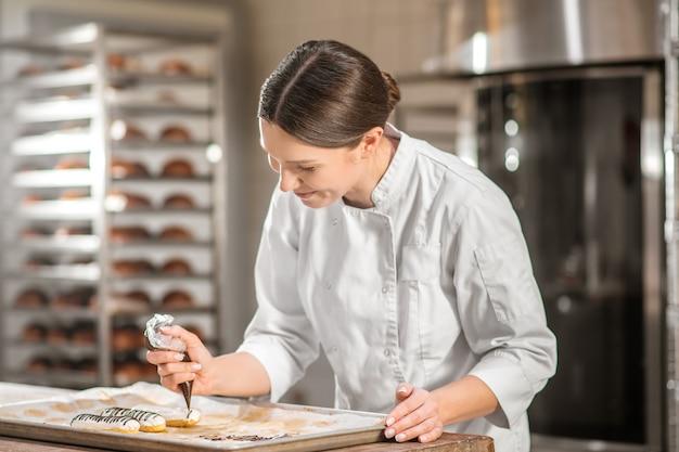 Dekorowanie ciast. uśmiechnięta ciemnowłosa kobieta koncentruje się z torbą ciasta pochylony nad tacą z ciastami dekorującymi powierzchnię
