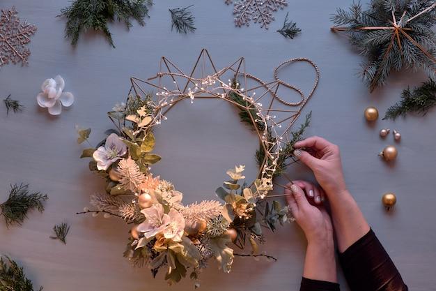 Dekorowanie drzwi świątecznym wieńcem. stonowany obraz kobiecych rąk mocujących sznurek do ręcznie robionego wieńca na metalowej podstawie