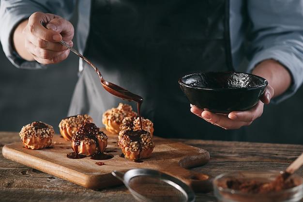 Dekorowanie pysznych domowych eklerek czekoladą i orzeszkami ziemnymi