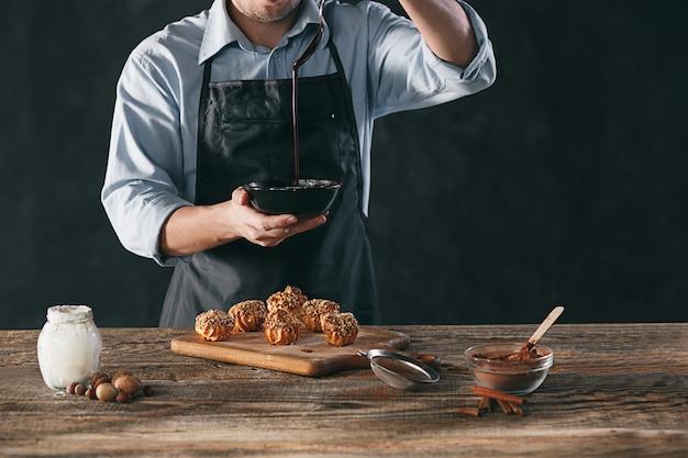 Dekorowanie pysznych domowych eklerów czekoladą i orzeszkami ziemnymi