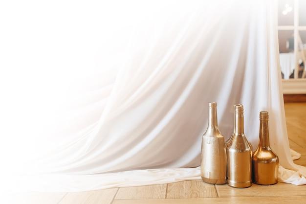 Dekorowanie stołu złotymi wazonami na butelki i tkaniną na bankiet weselny