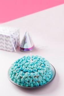 Dekorujący domowej roboty tort z świeczką na talerzu przeciw podwójnemu tłu