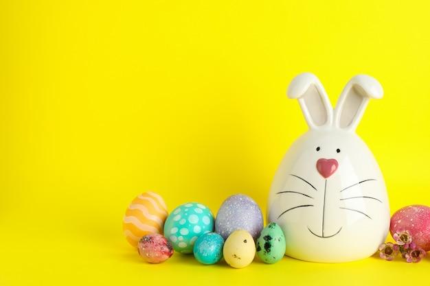 Dekorujący królik i wielkanocni jajka na koloru tle