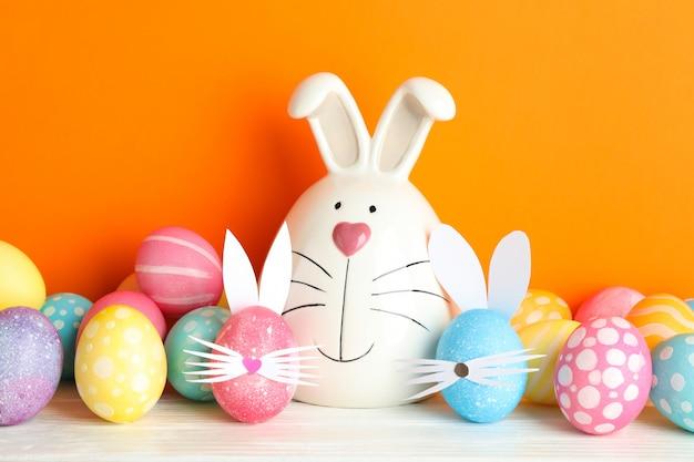Dekorujący królik i wielkanocni jajka na stole przeciw koloru tłu