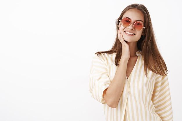 Delikatna atrakcyjna i stylowa młoda towarzyska kobieta o brązowych włosach w czerwonych okularach przeciwsłonecznych i białej letniej bluzce dotykająca twarzy i uśmiechnięta