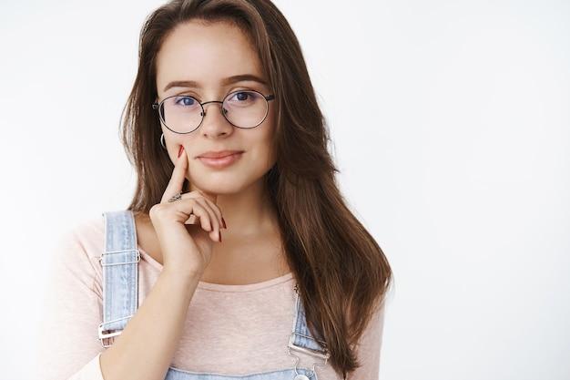 Delikatna atrakcyjna i zmysłowa młoda brunetka w przezroczystych okularach czuje się pewnie