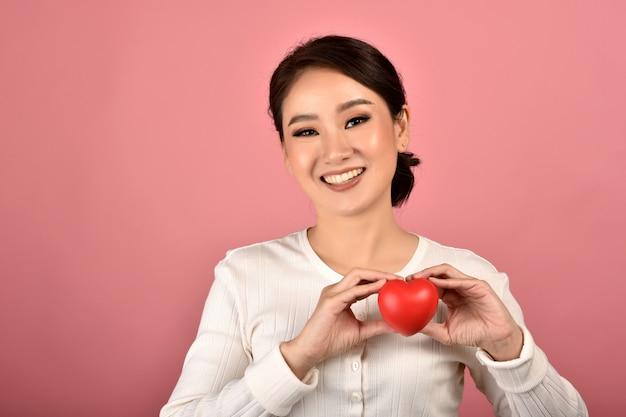 Delikatna azjatykcia kobieta trzyma czerwonego serce, szczęśliwa uśmiechnięta kobieta pokazuje miłość znaka wspierać i zachęcać, sprawdzać zdrowie serca.