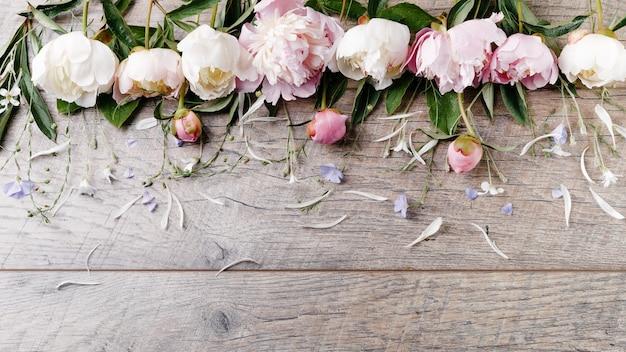 Delikatna biała różowa piwonia z płatkami kwiatów i białą wstążką na desce. widok z góry, układ płaski. skopiuj miejsce. koncepcja urodzin, matki, walentynek, kobiet, ślubu