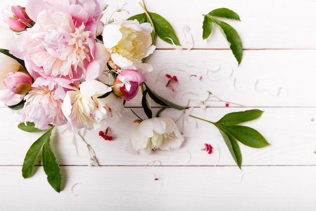 Delikatna biała różowa piwonia z płatkami kwiatów i białą wstążką na desce. widok z góry, układ płaski. skopiuj miejsce. koncepcja urodziny, matki, walentynki, kobiet, dzień ślubu.