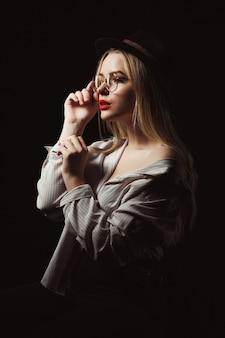 Delikatna blond modelka w okularach i kapeluszu, ubrana w koszulę z nagimi ramionami, pozuje z dramatycznym światłem w studio