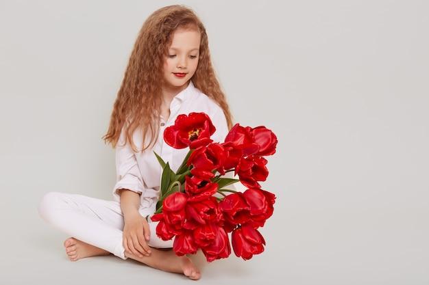 Delikatna blondynka z falującymi włosami siedzi na podłodze i patrzy na czerwone tulipany w dłoniach, z rozmarzonym wyrazem twarzy