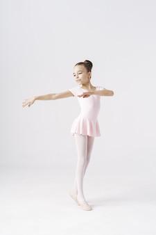 Delikatna dziewczyna baleriny stojący w pozie baletowej na białym. rodzaje koncepcji rozwoju osobowości.