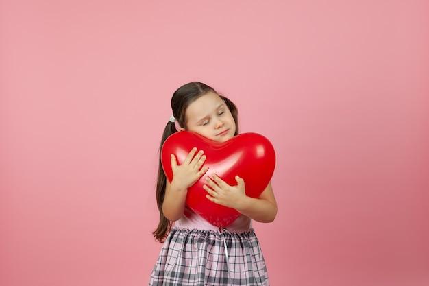 Delikatna dziewczyna w różowej sukience przytula czerwony balon w kształcie serca