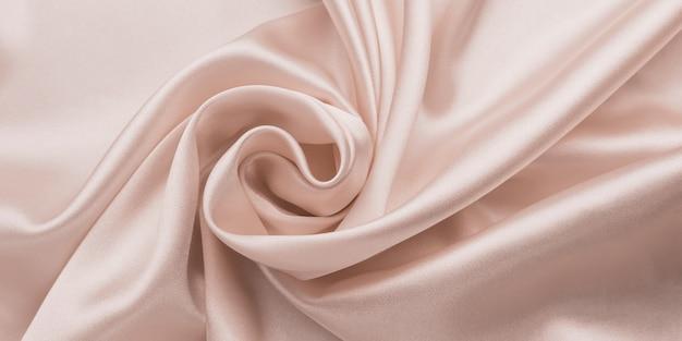 Delikatna gładka miękka różowa jedwabna pościel, streszczenie tło tkaniny z falami.