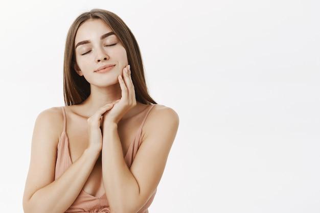 Delikatna i delikatna piękna europejska kobieta o pięknych rysach twarzy zamykająca oczy i uśmiechnięta zmysłowo dotykająca skóra delikatnie zachwycona produktem pielęgnacyjnym