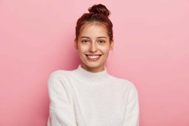 Delikatna, kobieca kobieta o niebieskich oczach, przyjemnie się uśmiecha, ma zębaty uśmiech, nosi biały wygodny sweter, patrzy prosto w kamerę, odizolowana na różowym tle