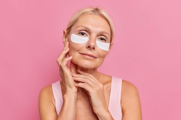 Delikatna kobieta w średnim wieku z jasnymi włosami dotyka twarzy czule nakłada łaty kosmetyczne pod oczy, aby zmniejszyć zmarszczki, nosi minimalny makijaż ubrana w t shirt ma zdrową skórę odizolowaną na różowej ścianie