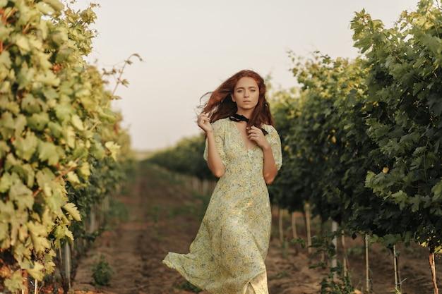 Delikatna kobieta z czerwoną falującą fryzurą i czarnym bandażem na szyi w długiej stylowej letniej sukience, patrząca z przodu na winnicę