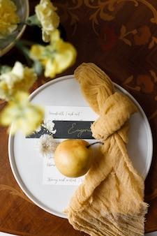 Delikatna kompozycja z żółtymi kwiatami i owocami z zaproszeniami ślubnymi wystrój ślubny