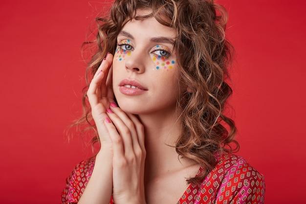 Delikatna ładna dama z romantyczną fryzurą i wielokolorowymi kropkami na twarzy, ubrana w pstrokaty wzorzysty top podczas pozowania, składająca ręce w pobliżu twarzy i delikatnie wyglądająca
