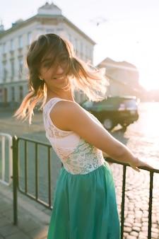 Delikatna młoda blondynka z uroczym uśmiechem pozuje o wschodzie słońca i blasku słońca