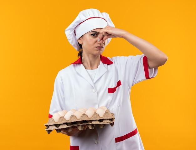 Delikatna młoda piękna dziewczyna w mundurze szefa kuchni trzymająca partię jajek z zamkniętym nosem