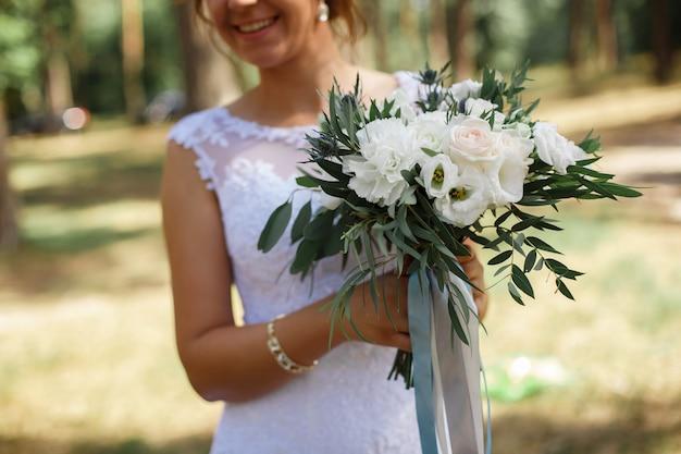 Delikatna panna młoda z bukietem kwiatów na zewnątrz. piękny ślubny bukiet białych i niebieskich kwiatów w rękach młodej pięknej panny młodej. dzień ślubu. szczegóły ślubu z bliska