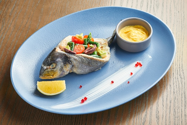 Delikatna pieczona ryba dorado z warzywami (pomidorami i szparagami) na niebieskim talerzu na drewnianej powierzchni. efekt filmowy podczas postu. nieostrość