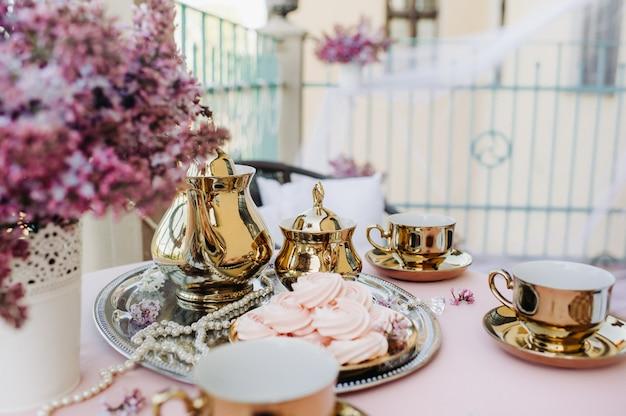 Delikatna poranna herbata na stole z liliowymi kwiatami, antycznymi łyżkami i naczyniami na stole z różowym obrusem.