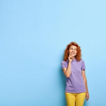 Delikatna rudowłosa nastolatka jest skupiona, ma wesoły rozmarzony wyraz twarzy, idealną skórę, uśmiecha się z dołeczkami