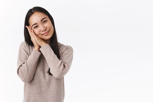 Delikatna urocza azjatycka ciemnowłosa kobieta w zimowym swetrze, przechylona głowa głupia i urocza, oparta na dłoniach i kontemplująca coś uroczego z czułością, dotknięta uroczą sceną, biała ściana
