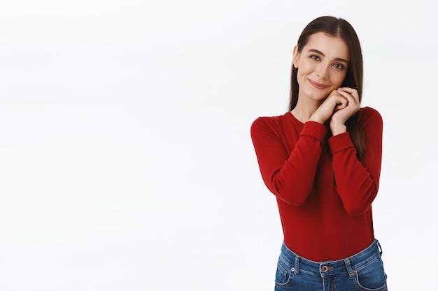 Delikatna, urocza ładna brunetka w czerwonym swetrze, otrzymuje miłą niespodziankę, przechyla głowę i składa dłonie razem przy twarzy, uśmiecha się rumieniąc się schlebia, wygląda na wdzięczną z czułością i troską