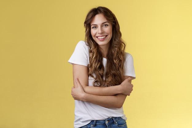 Delikatna urocza szczęśliwa przystojna dziewczyna długie kręcone włosy przytulić się chcę ciepłe przytulać uśmiechnięte zęby zadowolona przyjazna rozmowa dobrze się bawić nosić białą koszulkę obejmującą własne ciało żółte tło