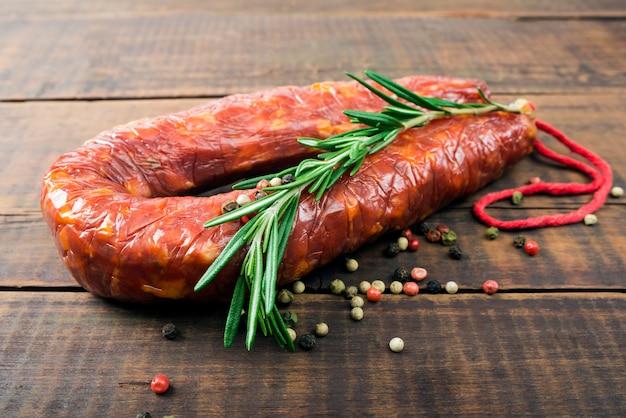 Delikatna wędzona kiełbasa (salami) na drewnianej desce