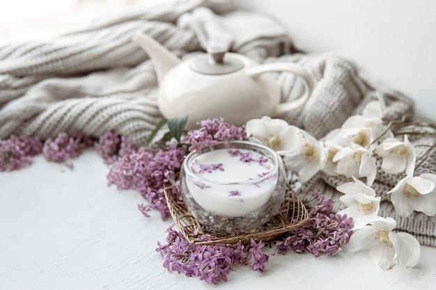 Delikatna wiosenna kompozycja ze świeżymi kwiatami, szklanką mleka i dzianinowym elementem.