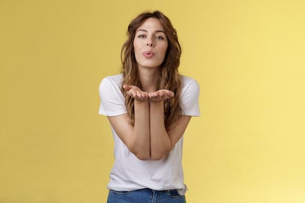 Delikatna zmysłowa zalotna romantyczna kobieca dziewczyna trzyma dłonie przy założonych ustach cios pocałunek aparat wyślij...