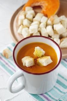 Delikatna zupa jarzynowa z dynią i grzankami i plasterkami dyni.