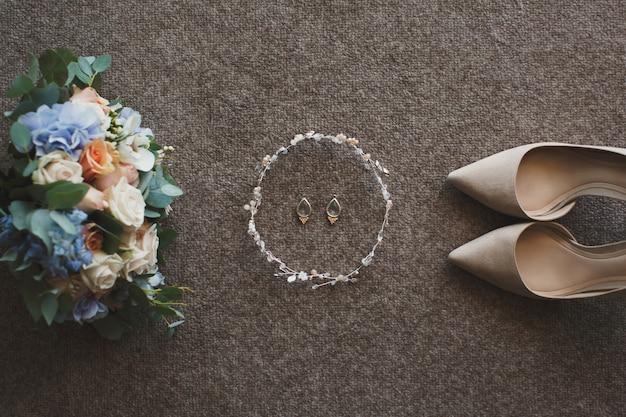 Delikatne beżowe buty i kolczyki ślubne oraz bukiet ślubny
