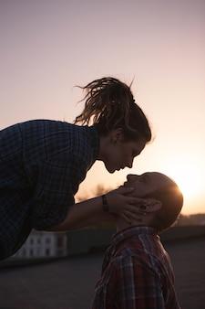 Delikatne całowanie para na zbliżenie tle zachodu słońca. romantyczna randka na świeżym powietrzu, zakochane biodrówki w centrum uwagi na pierwszym planie, koncepcja uczuć